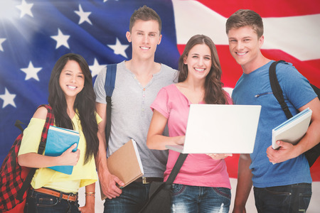 strips away: A smiling group of students holding a laptop while looking at the camera against close-up of us flag Stock Photo