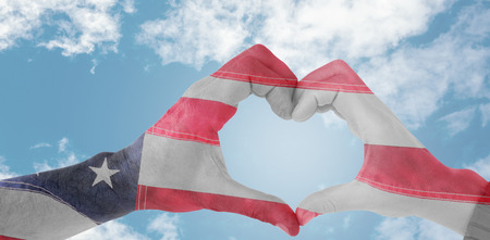 national identity: Couple making heart shape with hands against close-up of an flag