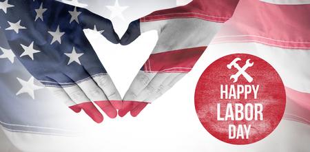 Mujer que hace la forma del corazón con las manos contra el marco completo de la bandera americana arrugada Foto de archivo - 83959919