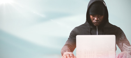 Serious male hacker with laptop  against full frame shot of painted wall Stock Photo