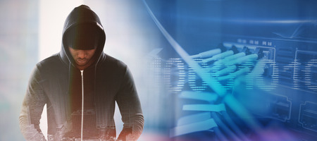 Spy in black hoodie against composite image of binary code on digital screen Stock Photo
