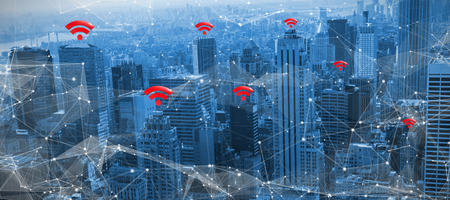 Red wifi symbol against view of cityscape Stock Photo