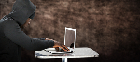 Male hacker using laptop on table  against brown textured background