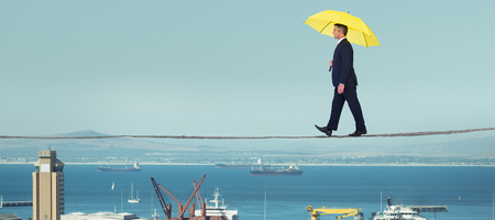 Businessman with yellow umbrella walking on white background against view of harbor
