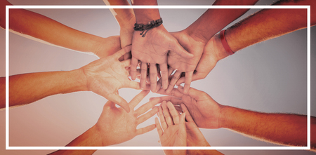 Directly below shot of friends stacking hands against clear sky Stock Photo