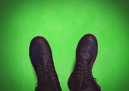 Digital composite of Black shoes on feet with green background