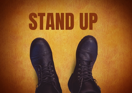 Digital composite of Stand up  text  and black shoes on feet with rustic brown  background