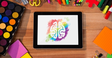 digitally generated image: Digital composite of Tablet on a school table with colored brain on screen Stock Photo