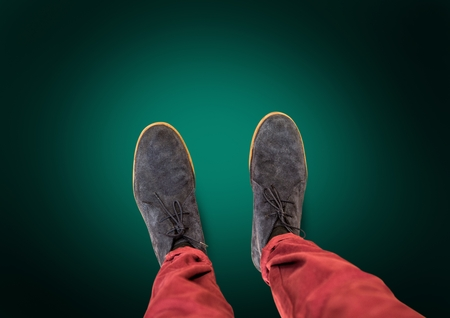 Digital composite of Grey shoes on feet with green background