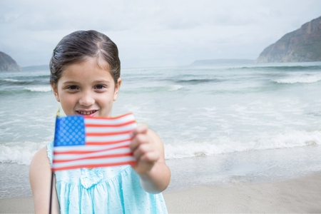 Digital composite of Girl holding a USA flag in the beach