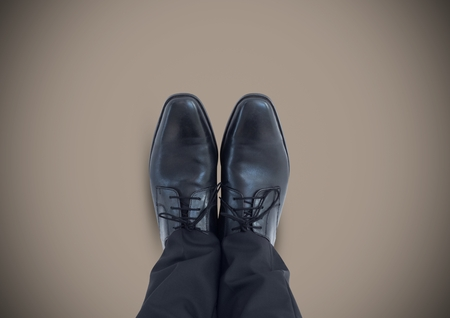 Digital composite of Black shoes on feet with brown background Stock Photo