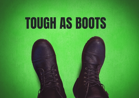 Digital composite of Tough as boots text and Black shoes on feet with green background