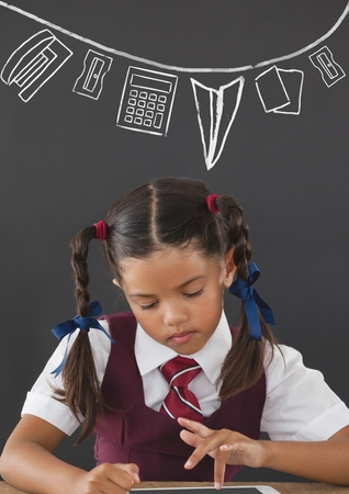 Digital composite of Student girl at table reading against grey blackboard with school and education graphic
