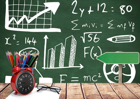 Digital composite of Desk foreground with blackboard graphics of formula equations Stock Photo
