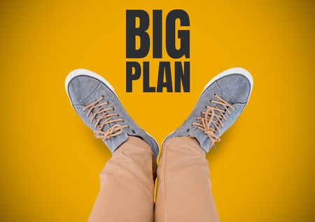 Digital composite of Big plan text and Grey shoes on feet with yellow background Stock Photo
