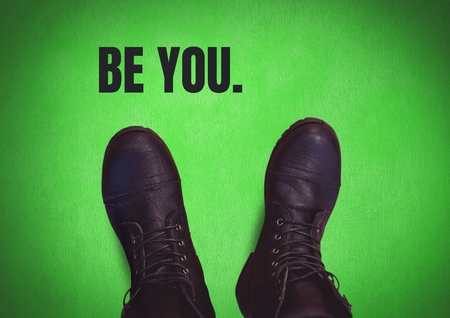 Digital composite of Be you text and Black shoes on feet with green background