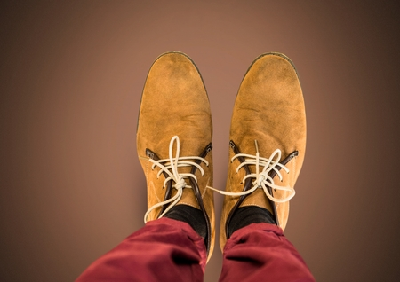 Digital composite of Brown shoes on feet with brown background