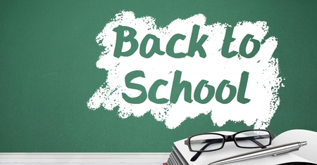 Digital composite of Back to school text on blackboard with glasses and book on desk