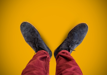 Digital composite of Grey shoes on feet with yellow background Reklamní fotografie