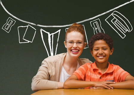 Digital composite of Student boy and teacher at table smiling against green blackboard with school and education graphic