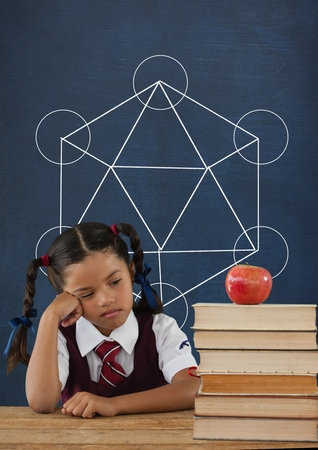 Digital composite of Sad student girl at table against blue blackboard with school and education graphic Stock Photo