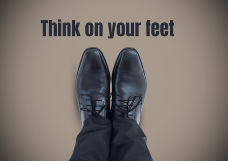 Digital composite of Think on your feet text and Black shoes on feet with brown background Stock Photo