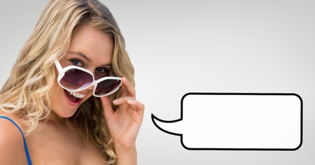 Digital composite of Surprised woman with speech bubble holding her sunglasses against grey background Stock Photo