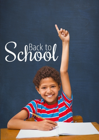 attending: Digital composite of Happy student boy at table raising hand against blue blackboard with back to school text