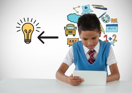 Digital composite of Schoolboy on tablet with education light bulb graphics