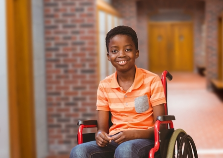 Digital composite of Disabled boy in wheelchair in school corridor Stock Photo