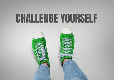 Digital composite of Challenge yourself text and Green shoes on feet with grey background