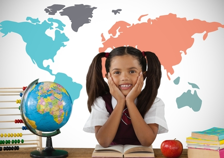 Digital composite of Schoolgirl at desk in front of colorful world map