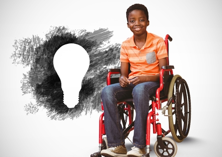 Digital composite of Disabled boy in wheelchair next to charcoal light bulb Stock Photo