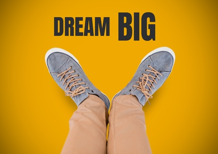 Digital composite of Dream Big text and Grey shoes on feet with yellow background Stock Photo