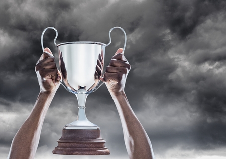 Digital composite of Man with a trophy on hands
