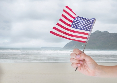 Digital composite of Person holding a USA flag in the beach Stok Fotoğraf