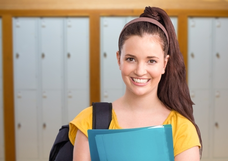Digital composite of female student holding folder in front of lockers