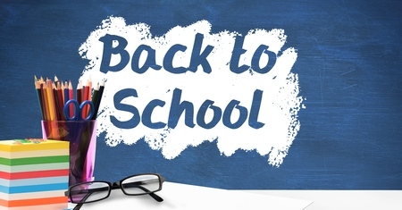 Digital composite of Desk foreground with blackboard graphics of Back to school Stock Photo