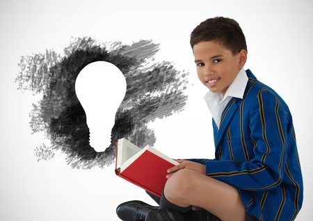 Digital composite of Boy reading next to charcoal light bulb