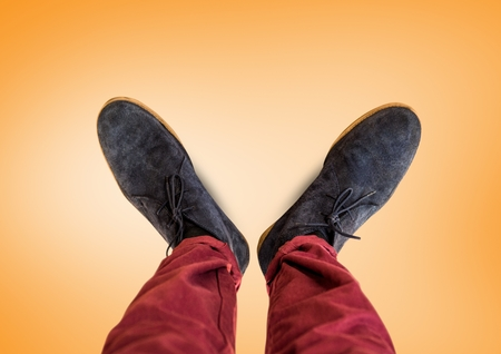 Digital composite of Grey shoes on feet with orange background