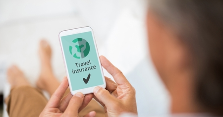 Digital composite of Man holding a phone with travel insurance concept on screen