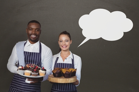 Digital composite of Small business owners couple with speech bubble holding cupcakes against grey background Stock Photo