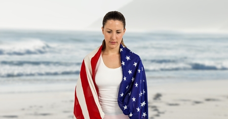 Digital composite of Woman holding a USA flag in the beach Stock Photo