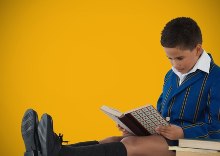 Digital composite of Boy reading in front of yellow background
