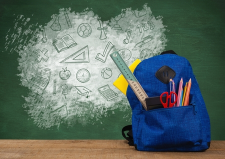 Digital composite of Schoolbag on Desk foreground with blackboard graphics of education icons drawings Standard-Bild