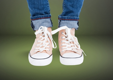 Digital composite of Beige shoes on feet with green background