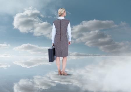Digital composite of Businesswoman holding briefcase under sky clouds