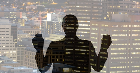 Digital composite of Business man silhouette against city