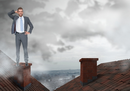 Digital composite of Businessman standing on Roofs with chimney and cloudy city Stock Photo