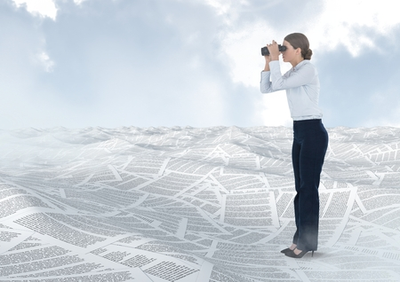 finding out: Digital composite of Businesswoman holding binoculars in sea of documents under sky clouds